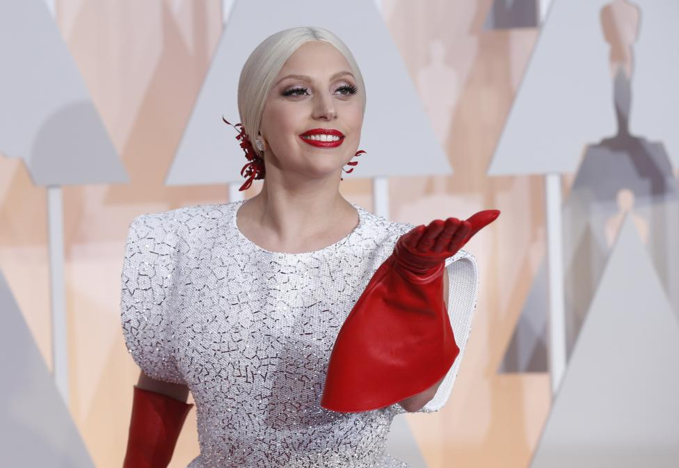 Singer Lady Gaga wears three custom-made Azzedine Alaia pieces and a white embellished gown with long red gloves as she arrives at the 87th Academy Awards in Hollywood, California February 22, 2015. REUTERS/Mario Anzuoni